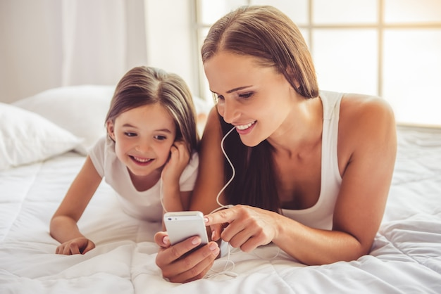 Woman and her daughter in earphones are listening to music
