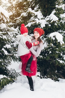 Woman and her daughter have fun in the winter forest