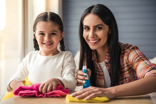 Woman and her daughter in protective gloves are smiling. cleaning concept