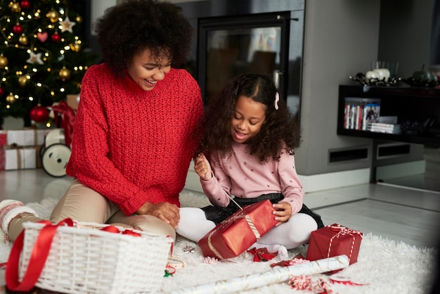 Woman and her daughter wrapping christmas presents