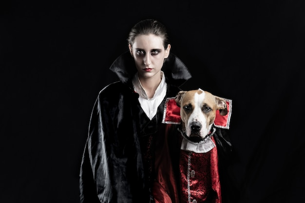 Woman and her dog in similar vampire costumes for halloween. young female and her pet puppy dressed up in matching dracula costume, posing in black studio background