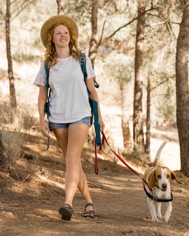 Woman and her dog walking in the woods