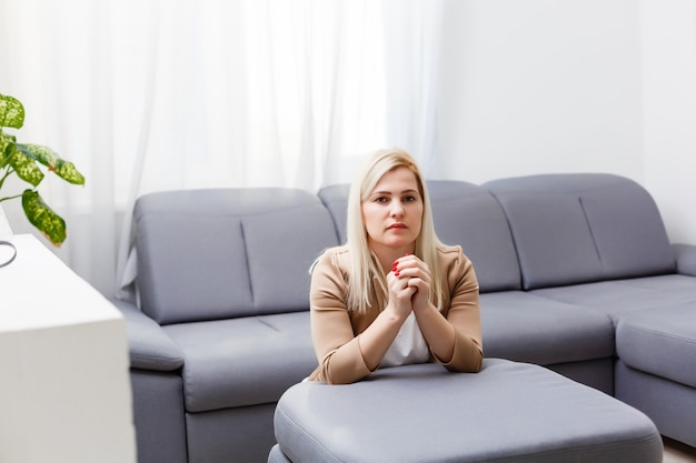 A woman on her knees prays at home