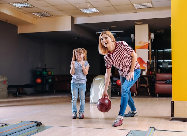Woman and her little daughter playing bowling in club