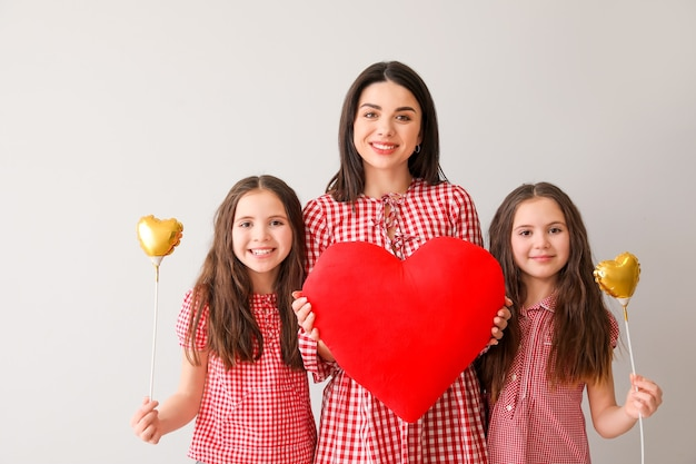 Woman and her little daughters with hearts on light. mother's day celebration