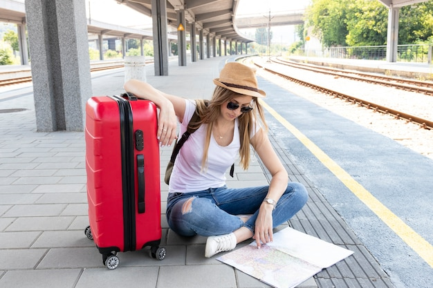 Woman and her luggage looking at a map