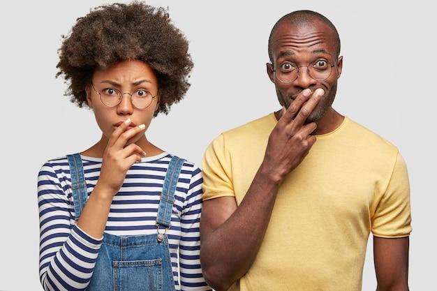 Donna e il suo amico uomo guardano scrupolosamente la fotocamera, tengono le dita sulle bocche