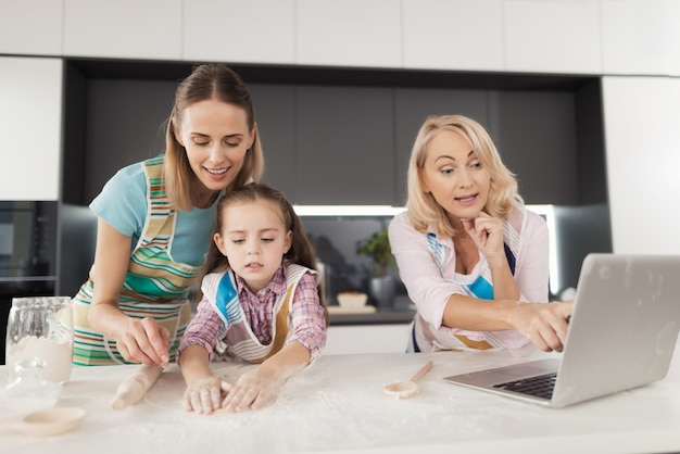 A woman and her mother are teaching their daughter to cook.