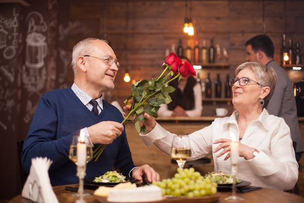 Woman in her sixties happy to recieve roses from her husband during dinner. senior couple date. fresh grapes. cheerful old couple.