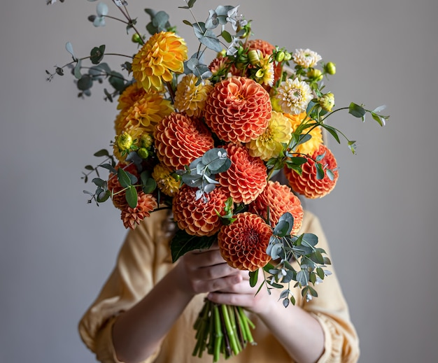 Woman hid her face with a bouquet of yellow and orange chrysanthemums, gray background, copy space.