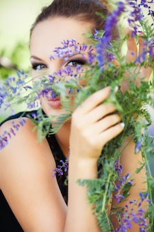 Woman hidden behind lilac flowers