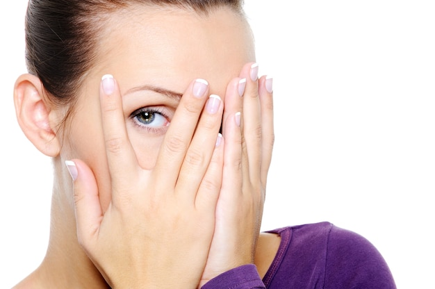 Женщина прячет лицо и смотрит сквозь пальцы