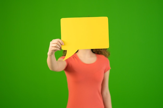 The woman hide her face by dialog sign on the green background