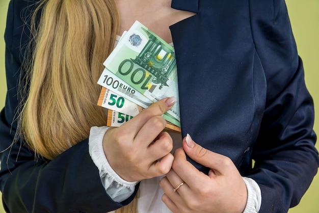 女性は緑に分離されたポケットユーロのお金を隠します