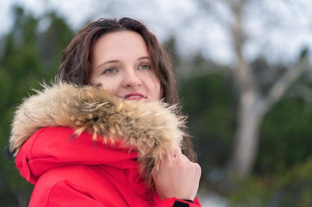 Женщина прячет лицо от холода в капюшоне красной зимней куртки. портрет на фоне хвойного леса