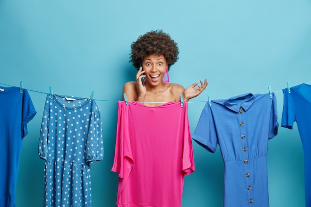 Woman hides naked body behind dress on clothesline chooses outfit to wear calls friends via smartphone prepares for special occasion isolated on blue