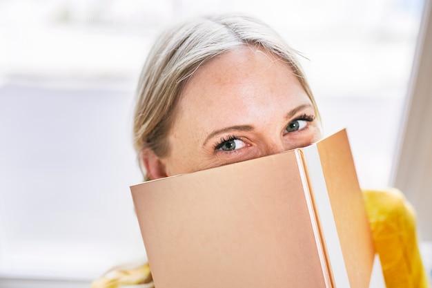 光沢のあるゴールドのノートの後ろに隠れている女性