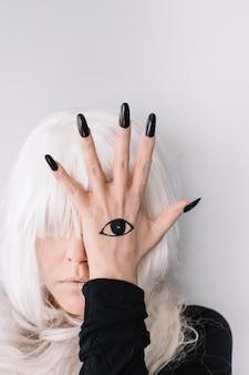 Woman hiding eye behind eye tattoo