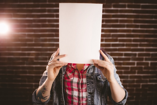 Woman hiding face from blank placard