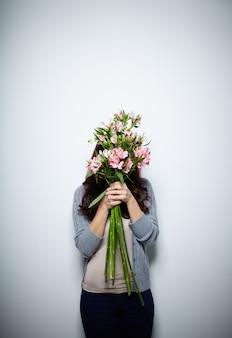 Woman hiding behind flowers