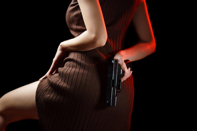 Woman hiding handgun behind her back