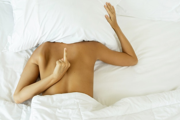 Woman hiding under the pillow and shows middle finger
