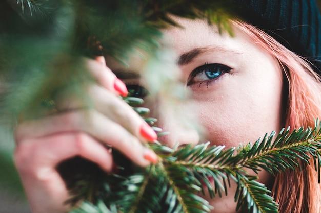 Woman hiding behind pine tree leaves