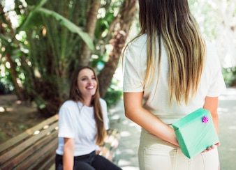 Woman hiding present behind back for her friend