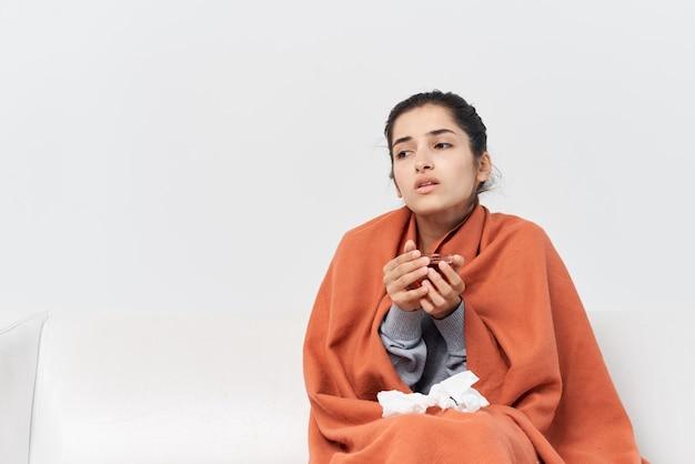自宅で毛布を持って隠れている女性一杯のお茶の感染治療