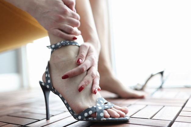 Woman in high heeled sandals holding her leg closeup