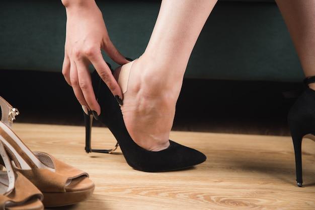 Woman in high heels glues a plaster