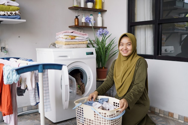 Woman in hijab doing clothing laundry at home using washing machine