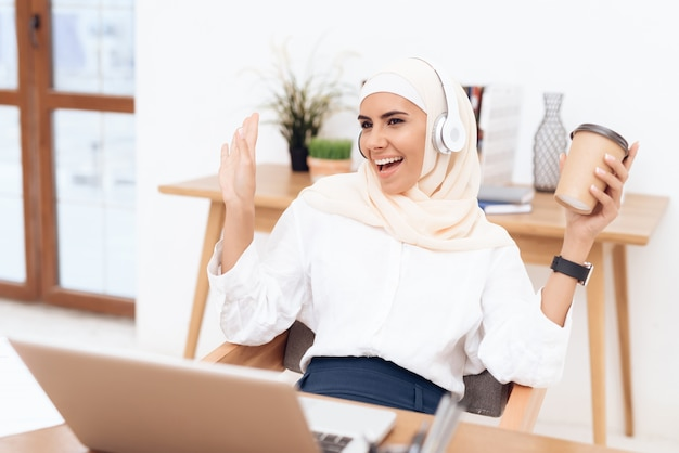 Woman in hijab listens to music on headphones