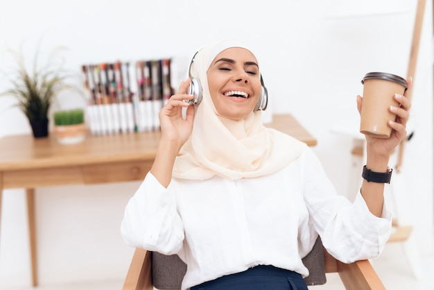 Woman in hijab listens to music on headphones.