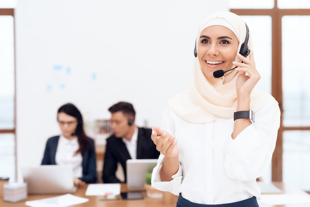 The woman in the hijab stands in the call center.