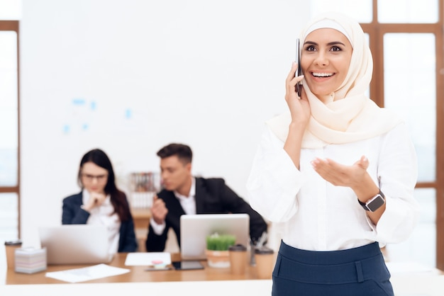 The woman in the hijab stands in the call center