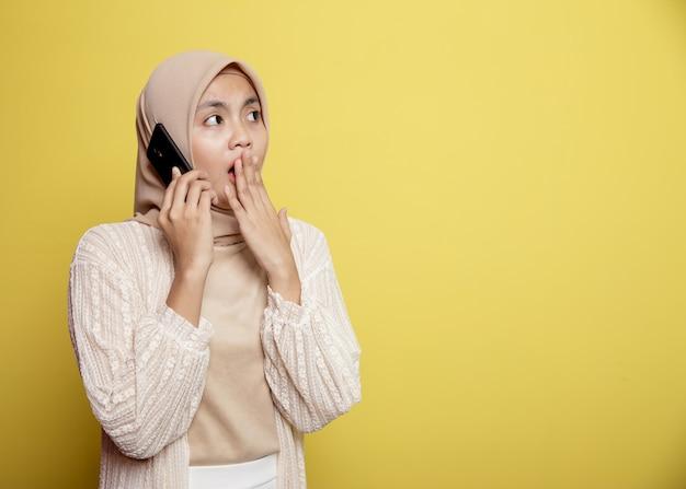 노란색 배경에 고립 된 호출 전화 충격 식 여자 히잡