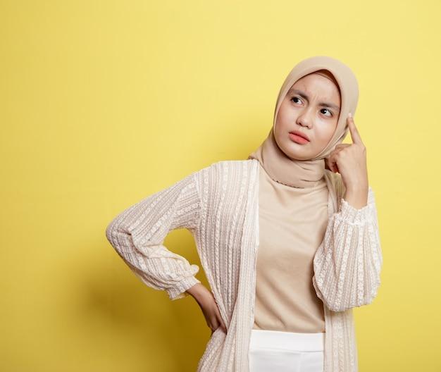 Женщина в хиджабе с выражением счастливого мышления что-то изолированное на желтом фоне