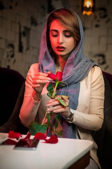 Woman in hijab with a rose in restaurant