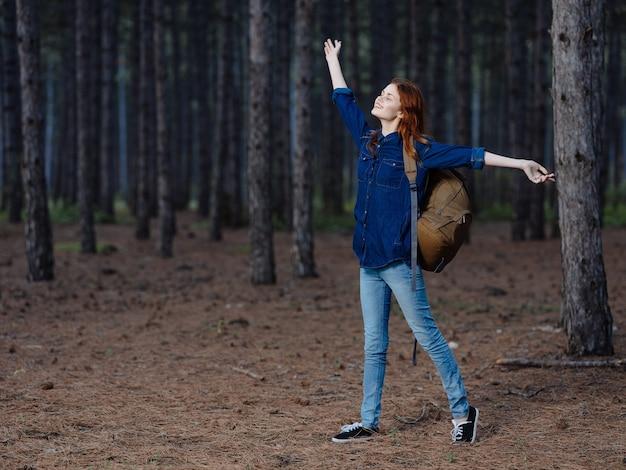 女性ハイカーは背の高い松の木の中で彼女の背中にバックパックを背負って森で休んでいます