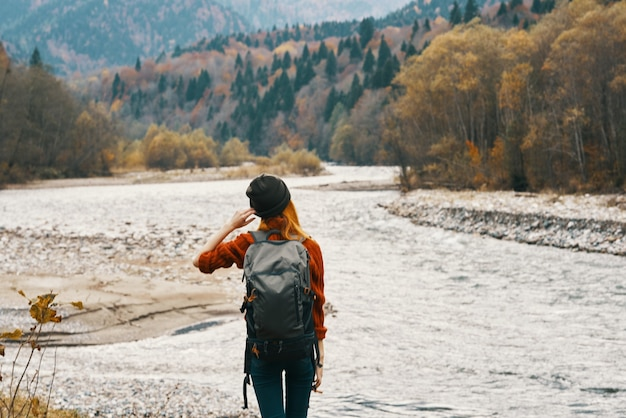 Woman hiker backpacker by the river in the mountains in autumn model travel