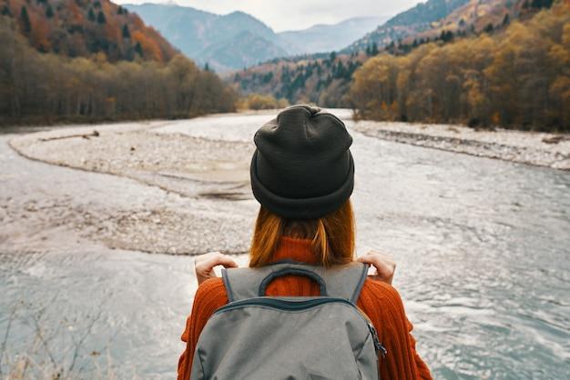 山の川沿いの女性ハイカーバックパッカー