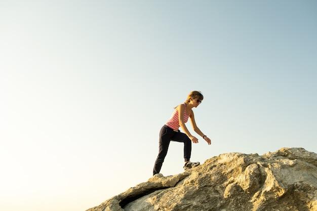 晴れた日に急な大きな岩を登る女性ハイカー。若い女性登山家は困難な登山ルートを克服します。自然のコンセプトでアクティブなレクリエーション。