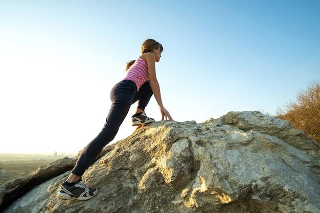 화창한 날에 가파른 큰 바위를 등반하는 여성 등산객. 젊은 여성 등반가는 어려운 등반 경로를 극복합니다. 자연 개념에서 활동적인 레크리에이션.