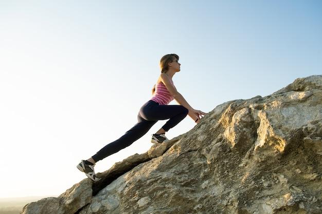 晴れた日に急な大きな岩を登る女性ハイカー。若い女性の登山家は、困難な登山ルートを克服します。自然の概念のアクティブなレクリエーション。