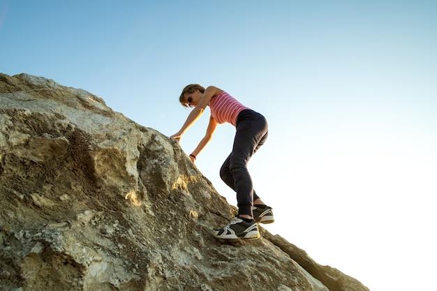 화창한 날에 가파른 큰 바위를 등반하는 여성 등산객. 젊은 여성 등반가는 어려운 등반 경로를 극복합니다. 자연 개념의 활동적인 레크리에이션.