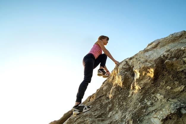 화창한 날에 가파른 큰 바위를 등반하는 여성 등산객