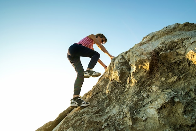 晴れた日に急な大きな岩を登る女性ハイカー