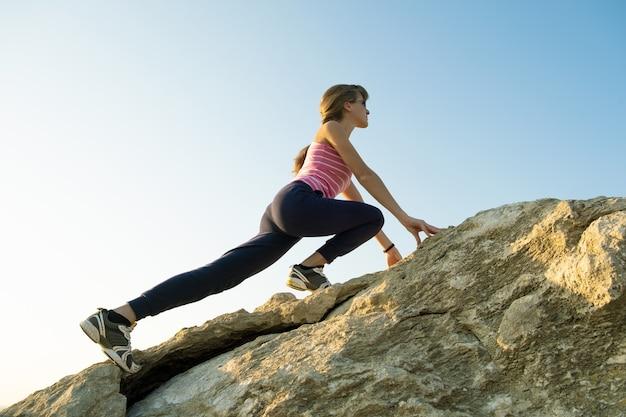 晴れた日に急な大きな岩を登る女性ハイカー。