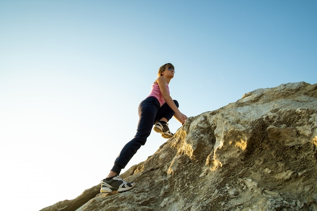 Woman hiker climbing steep big rock on a sunny day. young female climber overcomes difficult climbing route. active recreation in nature concept.